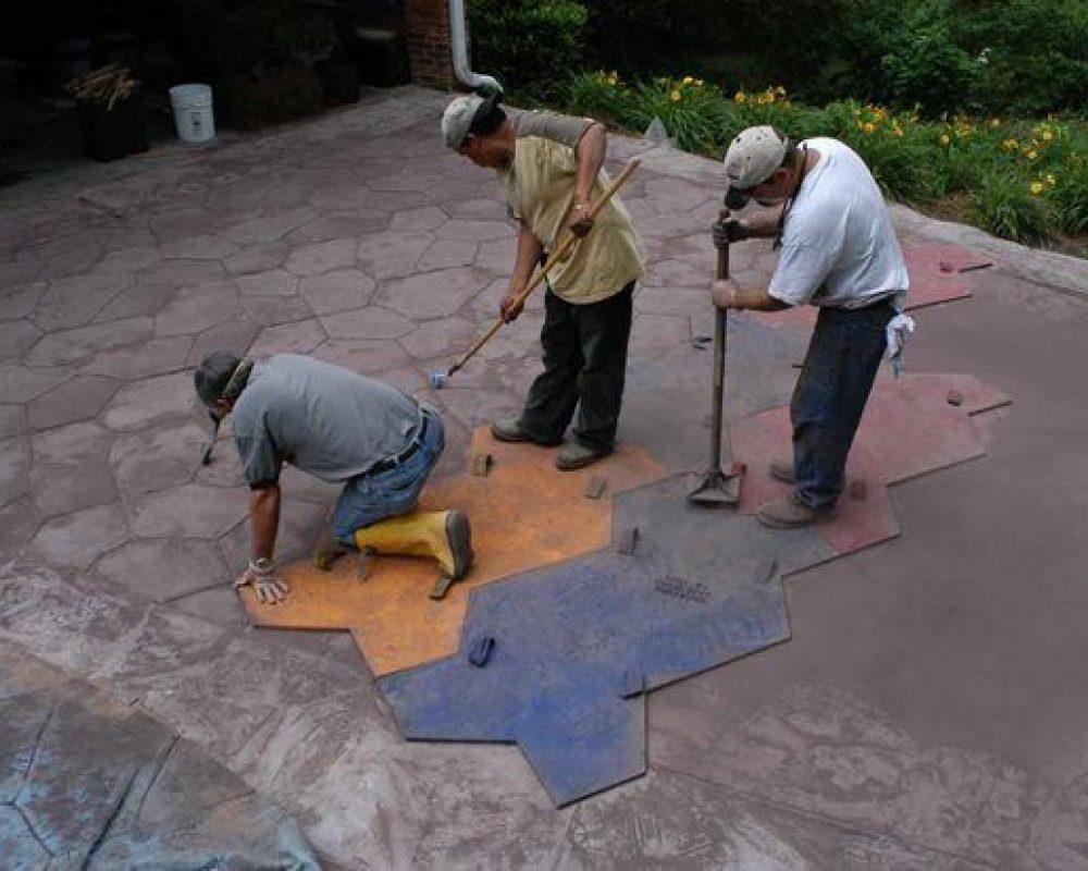 three concrete contractors fixing concrete floor